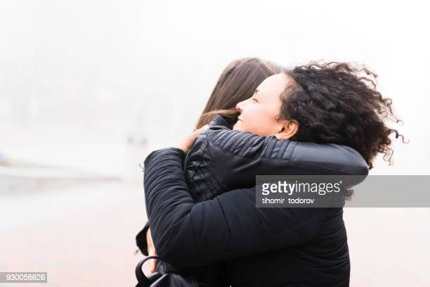 Curly-haired girl receiving a welcome back hug