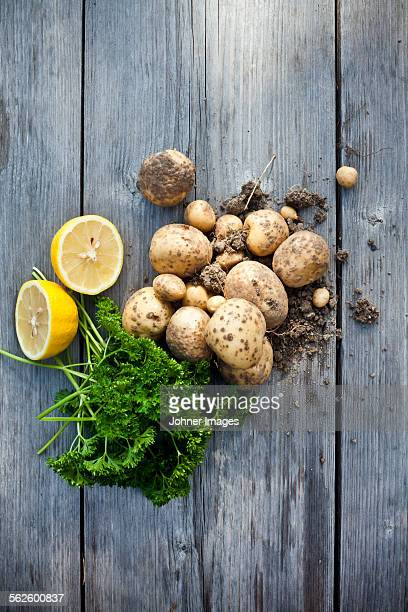 Curly-leaf parsley, lemons and potatoes on wooden background