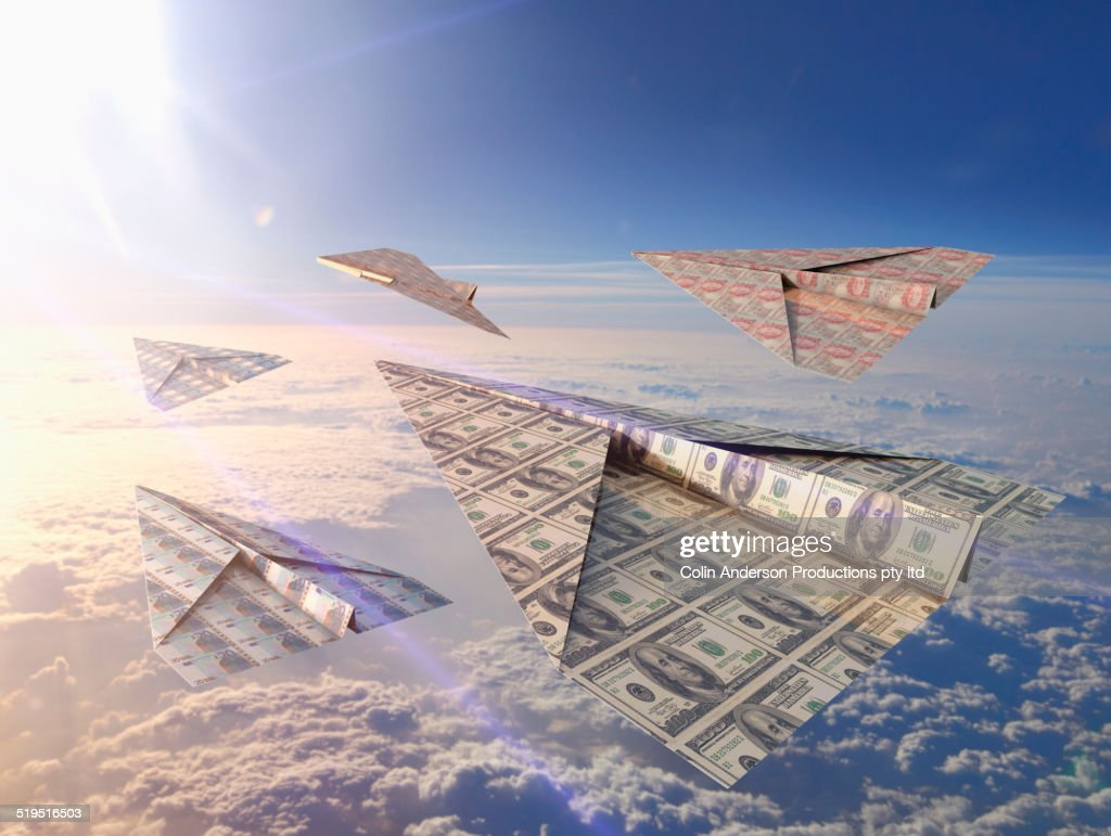 Currency bills folded into paper airplanes in atmosphere : Stock Photo