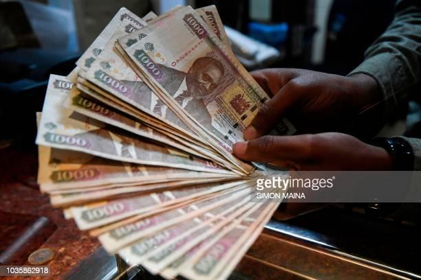 A currency dealer counts Kenyan shillings at a money exchange bureau on September 19 2018 in the Kenyan capital Nairobi