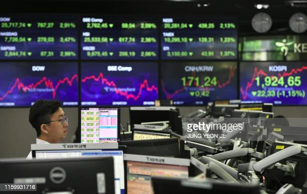 Currency dealer monitors exchange rates in a trading room at the KEB Hana Bank in Seoul on August 6, 2019. - The Chinese currency steadied on August...