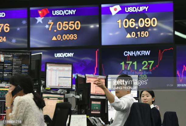Currency dealers monitor exchange rates in a trading room at the KEB Hana Bank in Seoul on August 6, 2019. - The Chinese currency steadied on August...