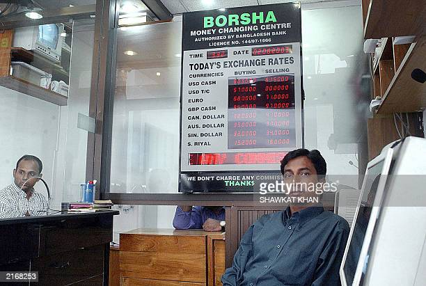 Currency exchange bureau employees wait for customers in Dhaka 02 June 2003 The Bangladeshi Taka passed its first crucial test relatively unscathed...