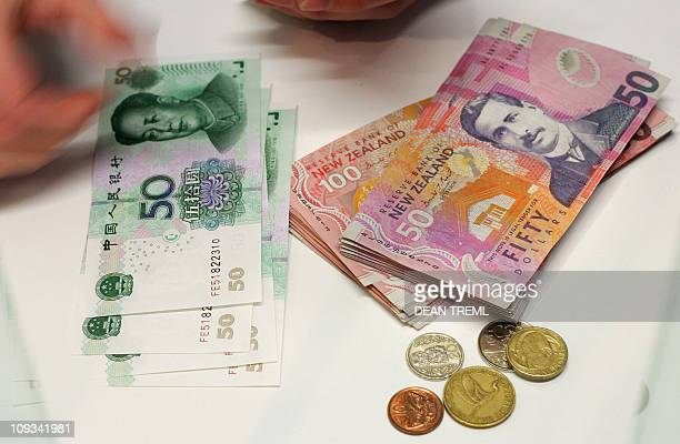 A currency exchange teller counts out Chinese Yuan alongside a stack of New Zealand dollars and coins in Auckland 21 April 2007 The New Zealand...