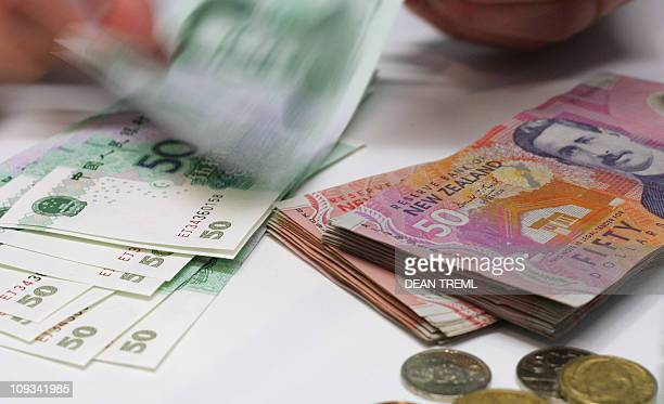 A currency exchange teller counts out Chinese Yuan alongside a stack of New Zealand dollars in Auckland 21 April 2007 The New Zealand dollar hit 7491...