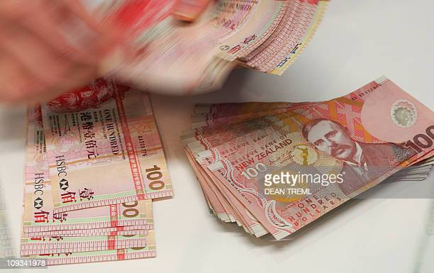A currency exchange teller counts out Hong Kong dollars alongside a stack of New Zealand dollars in Auckland 21 April 2007 The New Zealand dollar hit...
