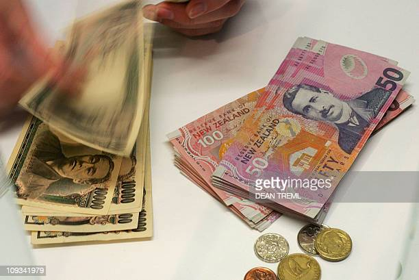 A currency exchange teller counts out Singapore dollars alongside a stack of New Zealand dollars in Auckland 21 April 2007 The New Zealand dollar hit...