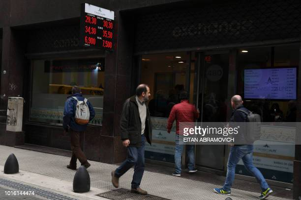 Currency exchange values are displayed in the buysell board of a bureau de exchange in Buenos Aires on August 13 2018 The fall of the Argentine...