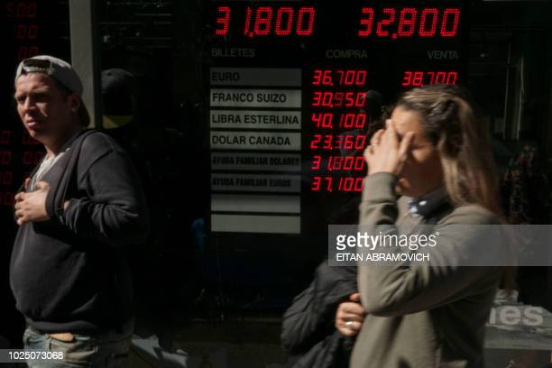 Currency exchange values are displayed in the buysell board of a bureau de exchange in Buenos Aires on August 29 2018 Argentina's President Mauricio...
