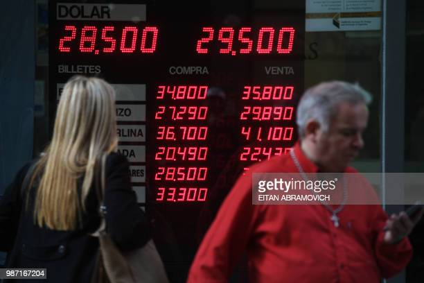 Currency exchange values are displayed in the buysell board of a bureau de exchange in Buenos Aires on June 29 2018 after the currency fell more than...