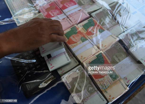 A currency exchange vendor adjusts Pakistani currency notes as he waits for customers on a street in Karachi on May 13 2019 Pakistan and the IMF have...