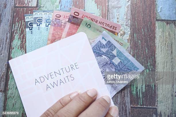 Currency Female hand holding Malaysian Ringgits inside a travel journal on a distressed painted wooden