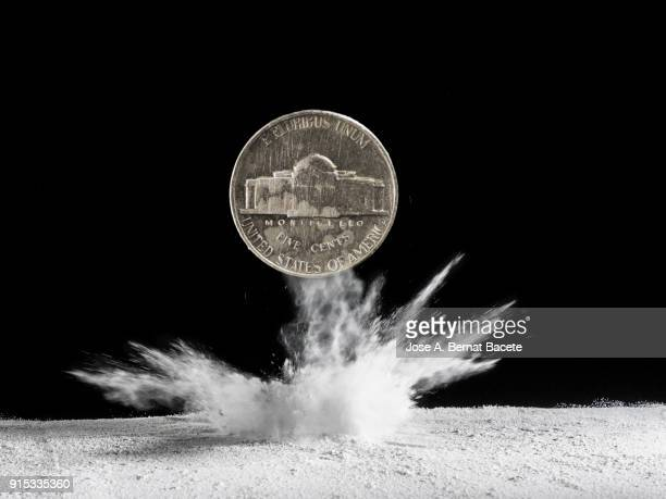 Currency of USA that falls and strikes on the soil with a great explosion of powder, on a black bottom. Concept of crisis of the currency US dollar.