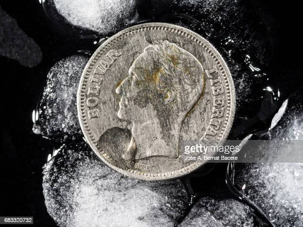 Currency of Venezuela of an Bolivar between chunks of ice, concept on the monetary crisis of the Venezuela