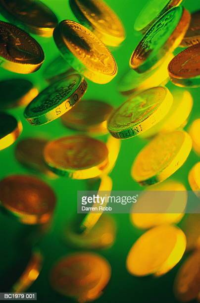 uk currency: one-pound coins in air (brightly lit) - gel effect lighting stock photos and pictures