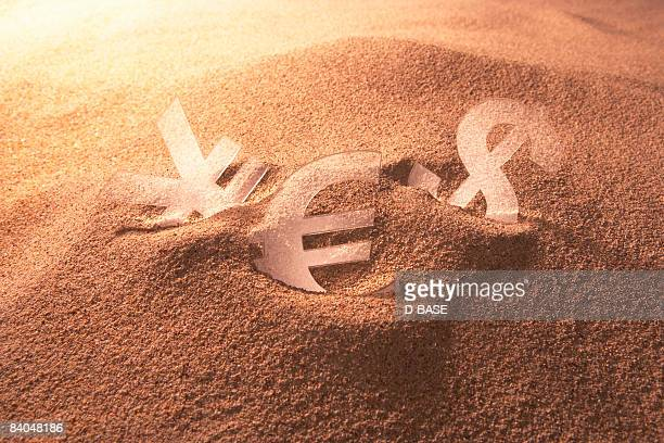 currency sign is buried in the sand