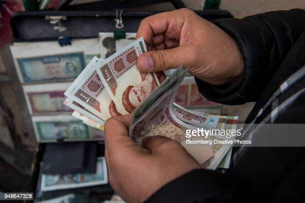 a currency trader counts iranian rial banknotes at a money exchange market - iran stock pictures, royalty-free photos & images