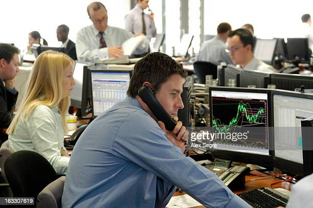 CONTENT] Currency trader in busy office looking at price fluctuations on computer screens in the City of London