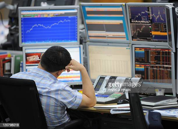 A currency trader monitors exchange rates in a dealing room at the Korea Exchange Bank in Seoul on August 11 2011 South Korean stocks rebounded...