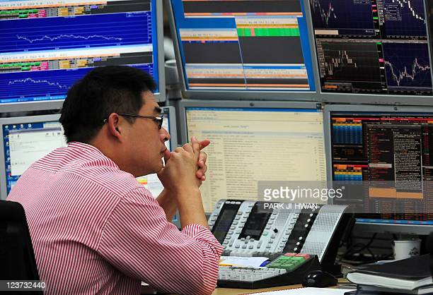 A currency trader monitors exchange rates in a dealing room at the Korea Exchange Bank in Seoul on September 5 2011 South Korean stocks opened...