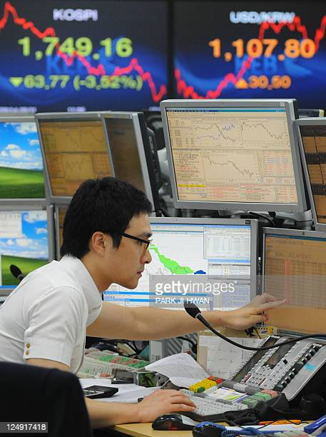 A currency trader monitors exchange rates in a dealing room at the Korea Exchange Bank in Seoul on September 14 2011 South Korean shares closed 352...