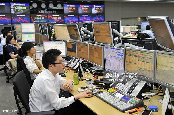 Currency traders monitor exchange rates in a dealing room at the Korea Exchange Bank in Seoul on August 5 2011 South Korean shares opened down 40...