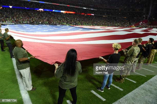 Current and former military personnel hold a large US flag on the field during the singing of the national anthem prior to a game between the Arizona...