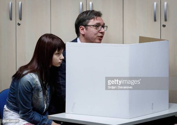 Current Serbian Prime Minister and presidential candidate Aleksandar Vucic accompanied by his daughter Milica prepares to cast his ballot at a...