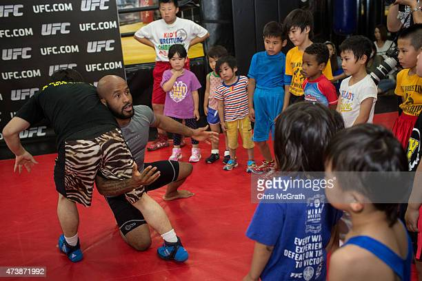Current UFC Flyweight Champion Demetrious Johnson gives instructions to young wrestling students during a class at Krazy Bee Gym on May 18 2015 in...