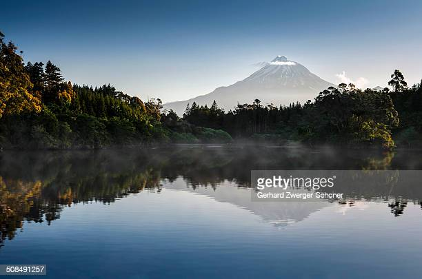 Currently inactive volcano, Mt Egmont, Mt Taranaki, reflections in Lake Mangamahoe reservoir, dam, North Island, New Zealand
