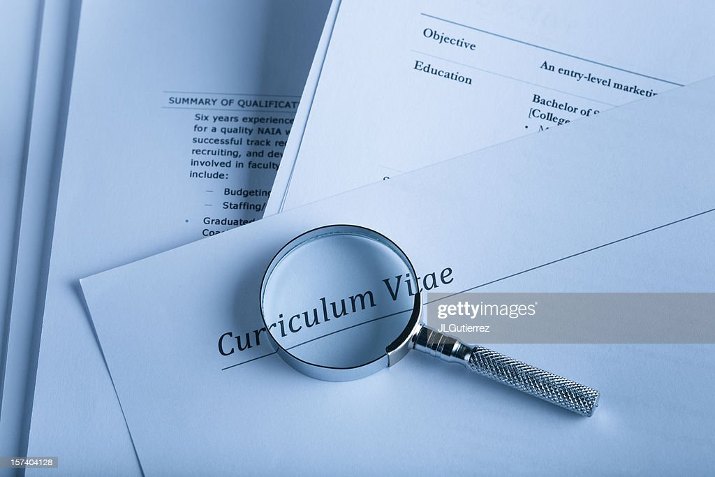 A curriculum vital and a magnifying glass : Stock Photo
