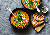 Curried red lentil tomato and coconut soup - delicious vegetarian food on grey background, top view. Flat lay served healthy lunch