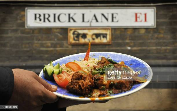 A curry dish is held up in front of a sign on Brick Lane in London on September 23 2009 The annual Brick Lane Curry Festival was launched Wednesday...