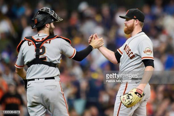 Curt Casali and Zack Littell of the San Francisco Giants celebrate after defeating the Milwaukee Brewers 5-4 at American Family Field on August 08,...
