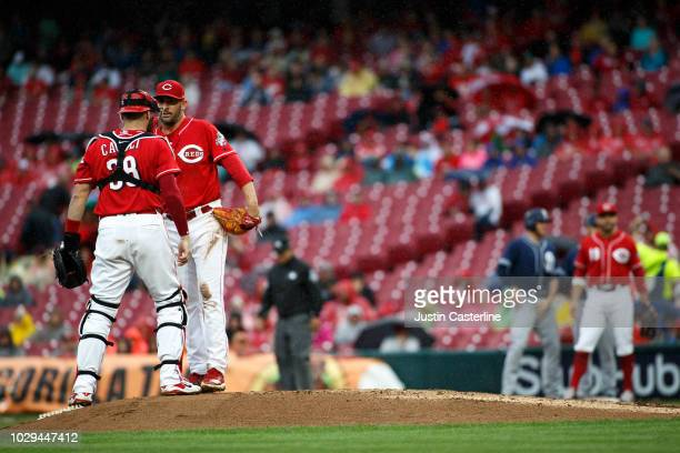 Curt Casali of the Cincinnati Reds talks with teammate Matt Harvey in the fifth inning during the game against the San Diego Padres at Great American...