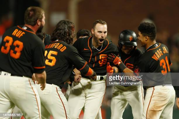 Curt Casali of the San Francisco Giants celebrates with teammates after hitting a walk-off RBI double in the bottom of the tenth inning against the...