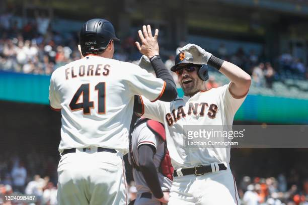 Curt Casali of the San Francisco Giants celebrates with Wilmer Flores after hitting a two-run home run in the bottom of the second inning at Oracle...