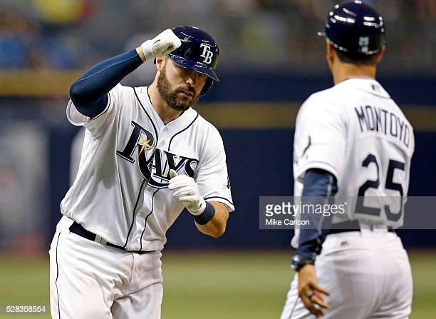 Curt Casali of the Tampa Bay Rays is congratulated on his home run by third base coach Charlie Montoyo during the seventh inning of a game against...
