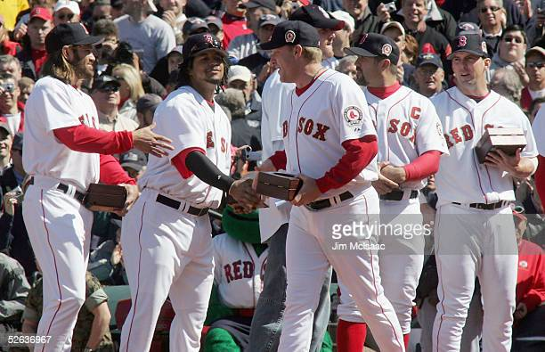 Curt Schilling of the Boston Red Sox makes his way down the line as he shakes hands with teammates Manny Ramirez and Johnny Damon after Bostons World...