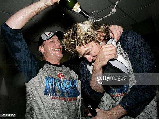 Curt Schilling of the Boston Red Sox pours champagne over teammate Bronson Arroyo in the locker room after their team defeated the New York Yankees...