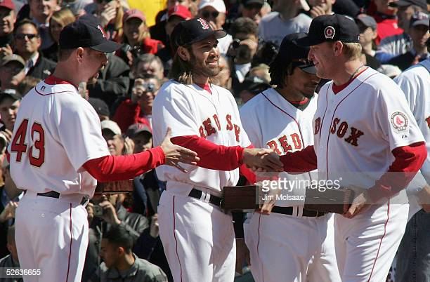Curt Schilling of the Boston Red Sox shakes hands with teammates Johnny Damon and Alan Embree after receiving his world series ring before they play...