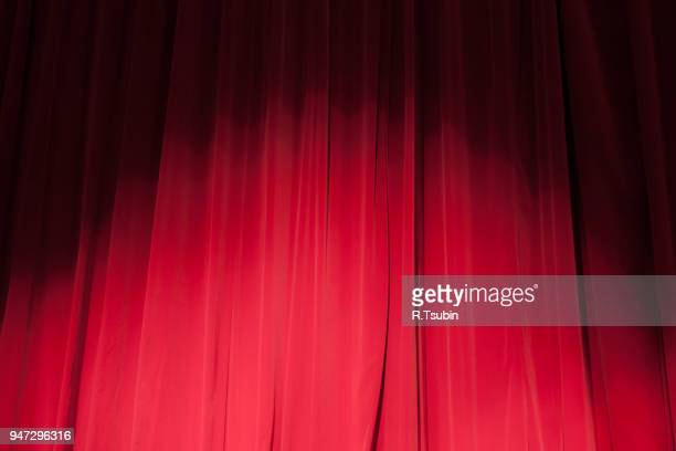 curtain from the theatre with a spotlight as background - spotlight film stock photos and pictures