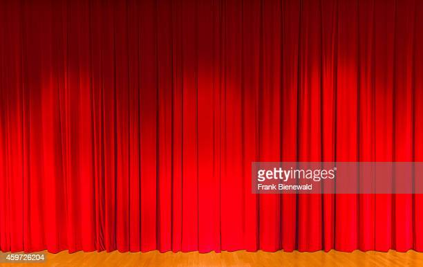 A curtain in dark red color covering a theater stage