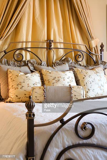 Curtains behind Headboard of Bed with Several Pillows