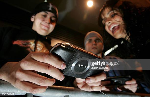 Curtis Anderson plays with a demonstration model of the new Sony PSP Playstation Portable gaming unit while waiting in line outside of the Sony Store...