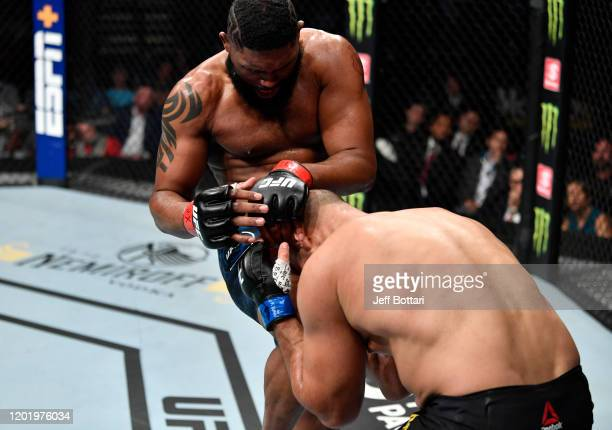 Curtis Blaydes knees Junior Dos Santos of Brazil in their heavyweight fight during the UFC Fight Night event at PNC Arena on January 25 2020 in...