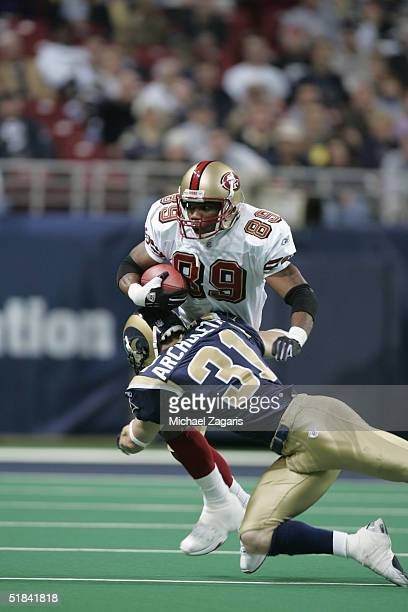 Curtis Conway of the San Francisco 49ers runs with the ball against Adam Archuleta of the St Louis Rams at the Edward Jones Dome on December 5 2004...