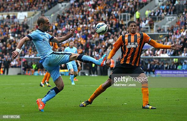 Curtis Davies of Hull City attempts to block a cross from Pablo Zabaleta of Manchester City during the Barclays Premier League match between Hull...