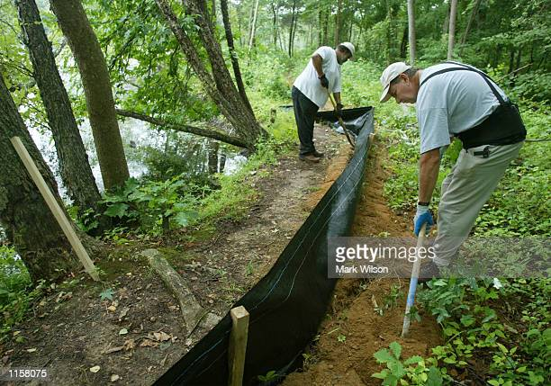 Curtis Davis and Robert Randall Department of Natural Resources workers install a silt fence that will surround a pond July 24 2002 in Crofton...