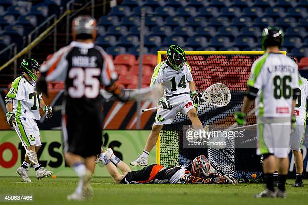 Curtis Dickson of the Denver Outlaws scores a diving goal during the third quarter as Drew Adams of the New York Lizards jumps above him during the...